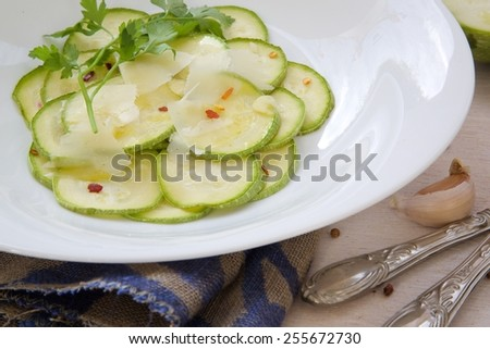 Light vegetarian lunch: oven baked zucchinis with garlic and Italian cheese parmesan. Ingredients on a white surface - stock photo
