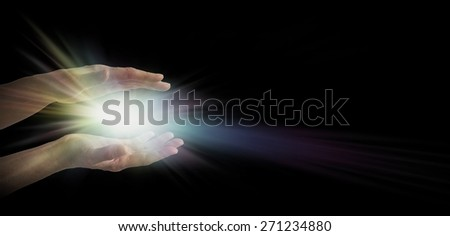 Light worker - pair of female hands emerging from the darkness with an explosion of white and rainbow tinted light energy between parallel hands  - stock photo