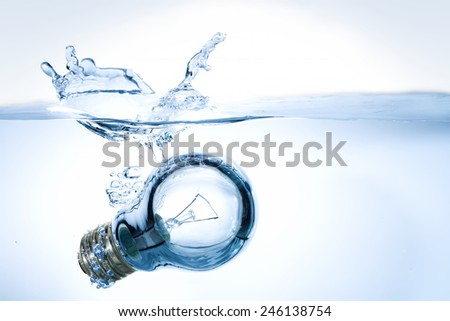 lightbulb falling into water - stock photo