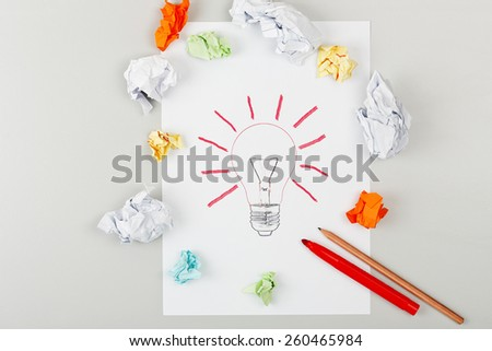 lightbulb surrounded by crumpled notes on desk surface - stock photo
