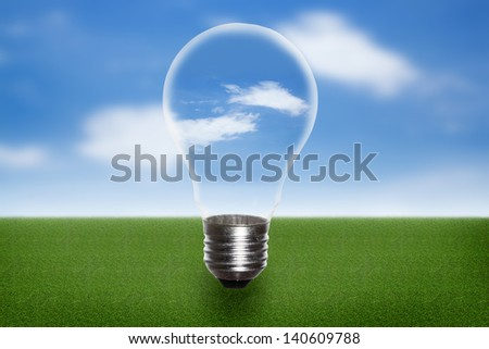 Lightbulb with green grass field and bright blue sky