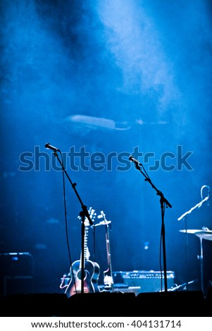 Lighted Empty Stage and Fog with Microphones and Guitar - stock photo