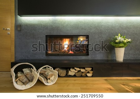 Lighted fireplace in wall with wood stocks
