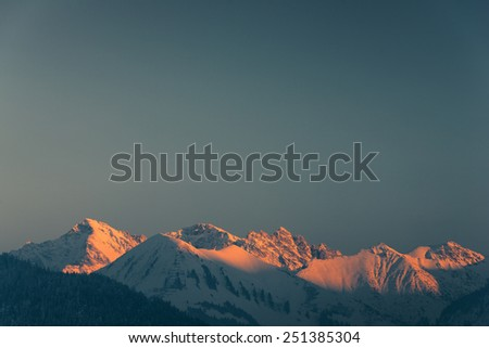 lighted mountain peaks with snow at winter in tirol - stock photo