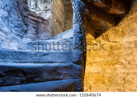 Lighted stone staircase in a medieval castle - stock photo