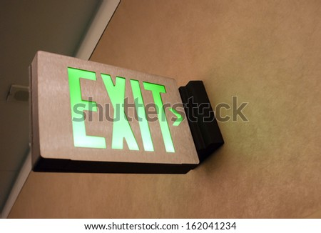 Lighted Wall Mounted Exit Sign Shows People Way Out Public Building - stock photo