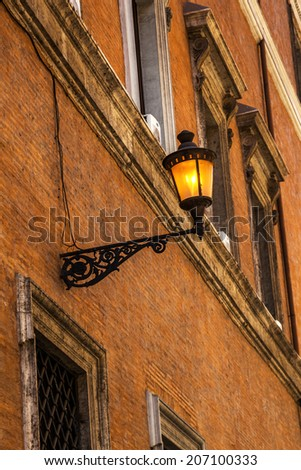 lightened street lantern at an old house facade in Rome, Italy