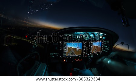 Lightened up cockpit and avionics in aircraft flying at night with beautiful twilight in background - stock photo