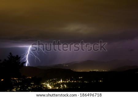 lightening bolts behind a city - stock photo