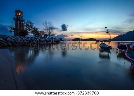 Lighthouse and boats by the sea during sunset - stock photo