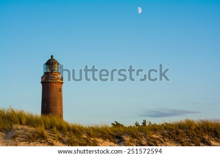 lighthouse and moon at Darss Peninsula in Germany - stock photo
