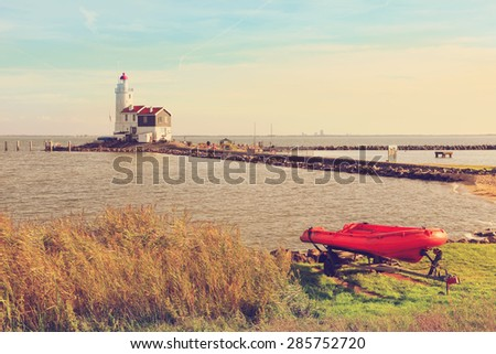 Lighthouse and red boat pastoral landscape on dutch seacoast (Marken.  Netherlands). Image done in vintage retro instagram style - stock photo