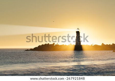 Lighthouse and surf boat with light beam at sunset