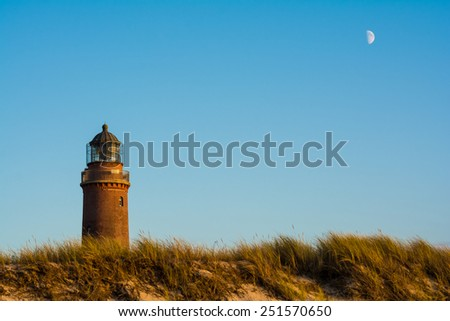 lighthouse and the moon at Darss Peninsula in Germany - stock photo