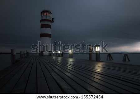 Lighthouse at Lake Neusiedl at cloudy night - stock photo