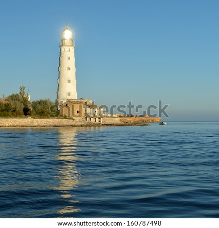 Lighthouse at sunset. The sun's reflection in the lens of the lighthouse