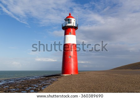 Lighthouse at the coast in The Netherlands, surrounded by sea and a dike - stock photo