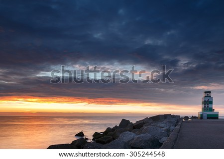 Lighthouse at the North Sea standing in evening sunset  - stock photo