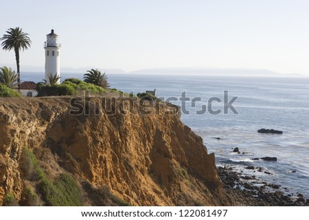 Lighthouse atop of a rugged cliff by the seashore