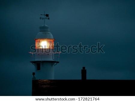 lighthouse beacon at night - stock photo