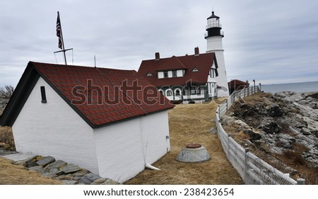 lighthouse by the ocean in the evening - stock photo
