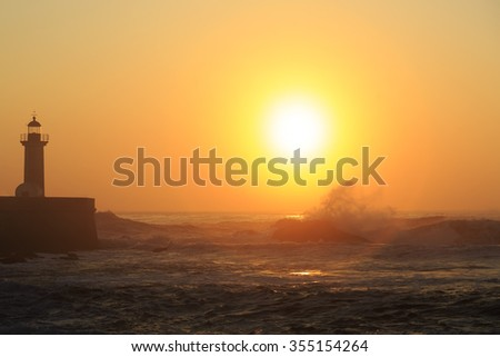 Lighthouse Felgueirasin Porto with wave splash at sunset, Porto, Portugal  - stock photo
