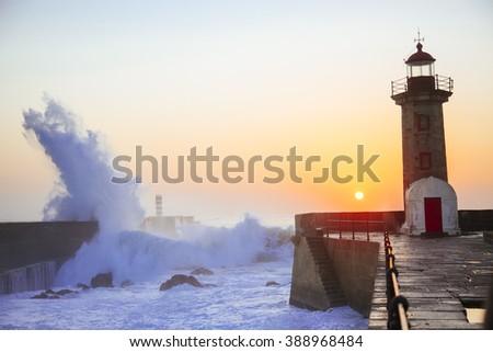 Lighthouse Felgueirasin Porto with wave splash at sunset, Porto, Portugal - stock photo