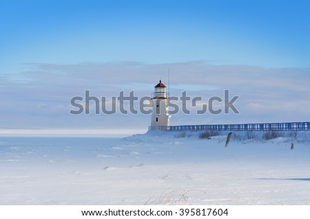Lighthouse in a calm and desolate winter landscape.