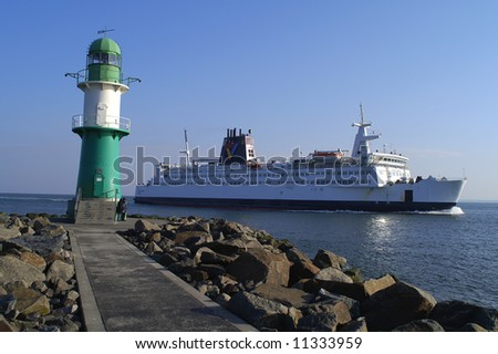 lighthouse in rostock against ferry - stock photo