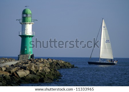 lighthouse in rostock against yacht - stock photo