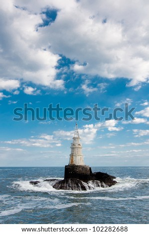 Lighthouse in stormy waves - stock photo