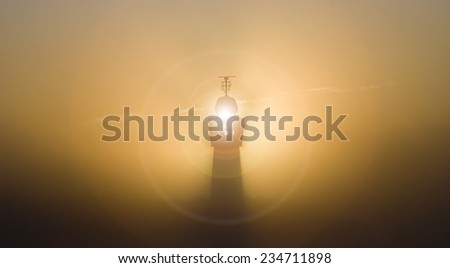 lighthouse in the fog obscuring sunrise - stock photo