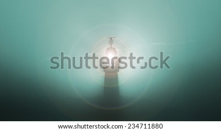 lighthouse in the fog obscuring sunrise, colorized - stock photo