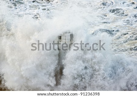 Lighthouse of Camogli (Italy) during a powerful sea storm - stock photo