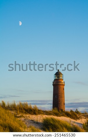 """lighthouse of """"Darsser Ort"""" and the moon at the Baltic Sea Germany - stock photo"""