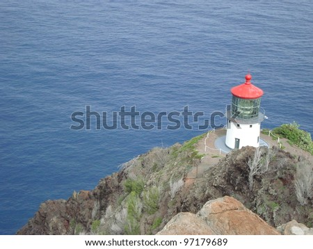 Lighthouse off the coast of Oahu, Hawaii on top of mountain near rocks