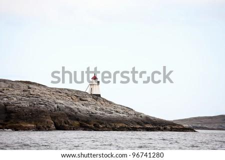 Lighthouse on a rocky coast - stock photo