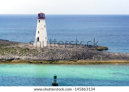Lighthouse on an island on a cloudy day with a channel buoy in the foreground  - stock photo