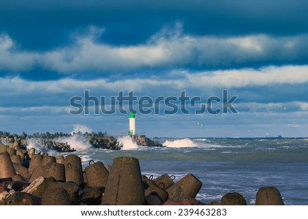 Lighthouse on breakwater in storm, Ventspils, Latvia.