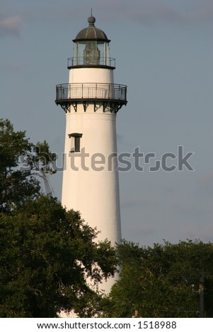 Lighthouse on coast with sky and trees in background