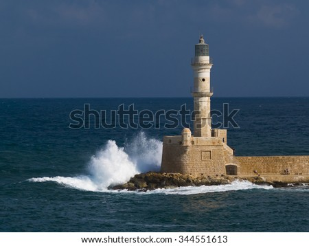 Lighthouse on harbor wall with crashing wave