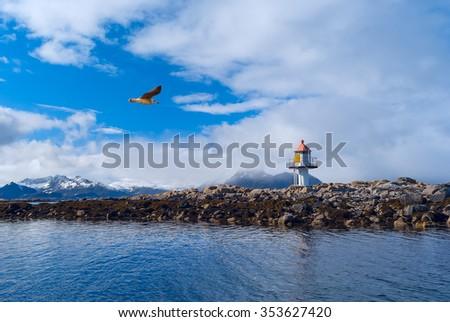 Lighthouse on the island in Norwegian sea - stock photo