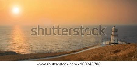 Lighthouse on the ocean beach at sunrise - stock photo