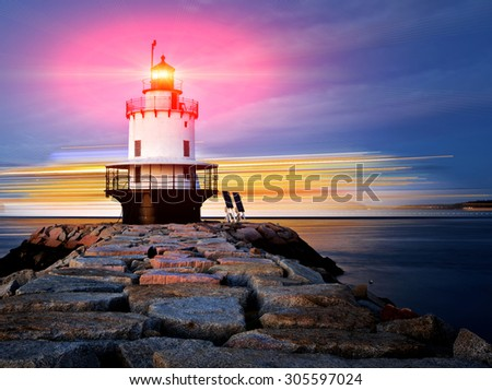 Lighthouse on top of a rocky island slow exposure with added lens flare - stock photo