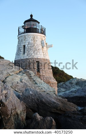 Lighthouse on top of rocky cliff at dusk - stock photo