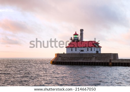 Lighthouse Overlooking at Lake Superior, at sunrise with pink clouds - stock photo