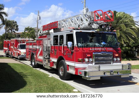 LIGHTHOUSE POINT, FLORIDA - FEBRUARY 12, 2014: One large, modern red fire engine truck with ladder and two red ambulances parked on a street responding to a call in a neighborhood on a sunny day.