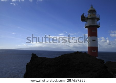 Lighthouse,Punta de Teno, on the Canary Island of Tenerife, giant moles of volcanic rock ending in the Atlantic Ocean, from blue waters are common whale sightings