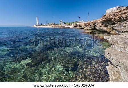 Lighthouse, sea and rock, blue sky. Crimea. Ukraine - stock photo