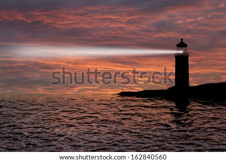 Lighthouse searchlight beam through marine air at night  - stock photo